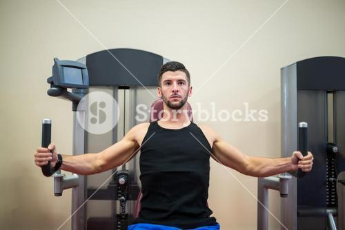 Focused man working out on the weights machine