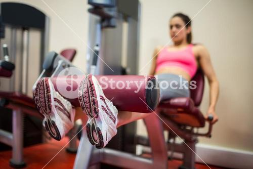 Focused woman using a weights machine
