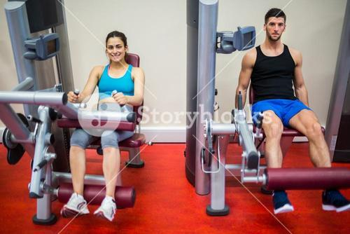 Man and woman both using weights machine