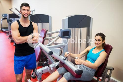 Smiling woman sitting in the weights machine