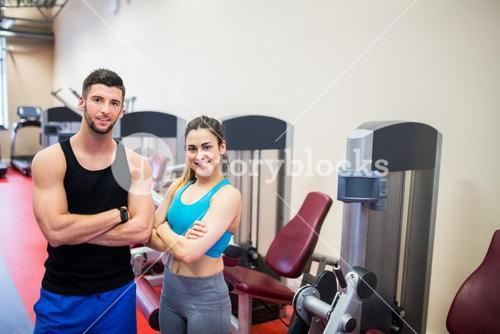 Woman and her trainer by the weights machines