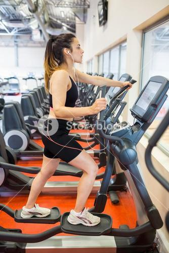 Focused woman on the ellipitical machine