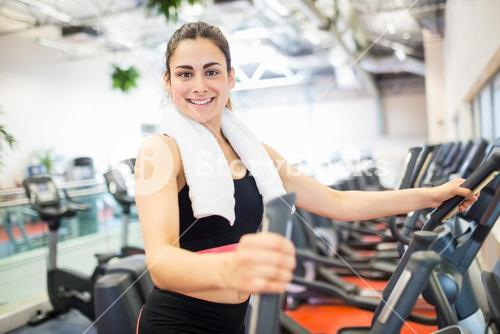 Smiling woman on the cross trainer