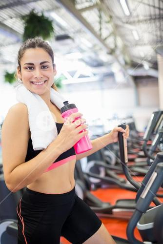 Smiling woman drinking on the cross trainer