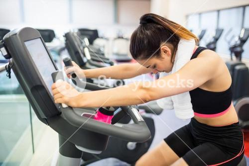 Exhausted woman on the exercise bike