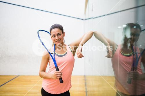 Smiling woman holding a squash racket