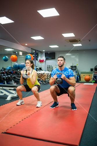 Couple crouching down while holding kettlebells