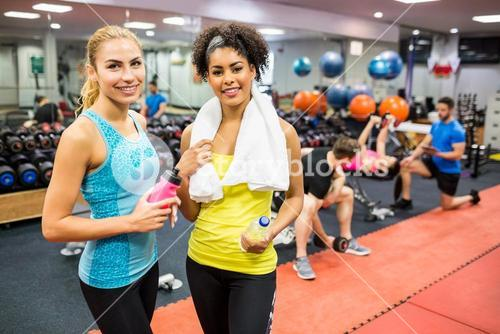 Fit women chatting in weights room