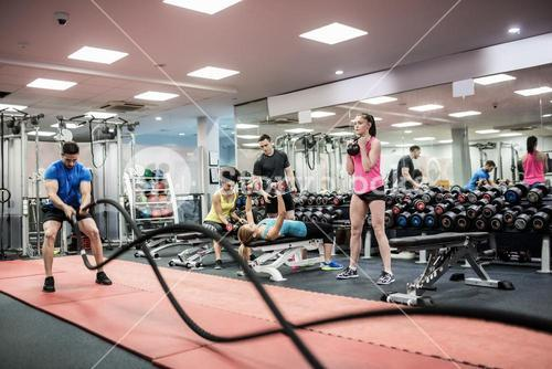 Fit people working out in weights room