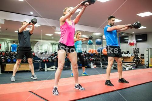Fit people swinging kettlebell weights