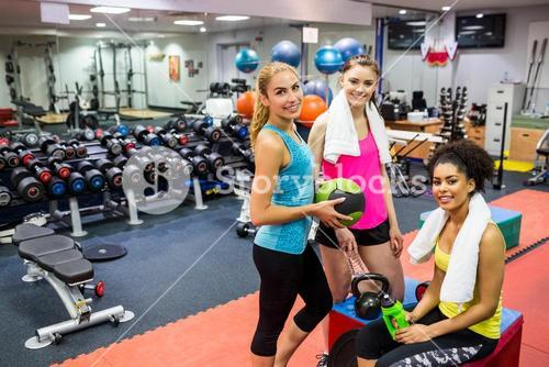 Fit women smiling in weights room