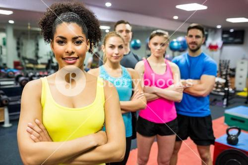 Fit people smiling at camera in weights room