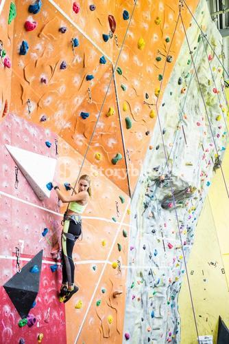 Fit blonde rock climbing indoors