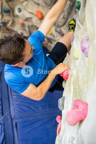 Fit man rock climbing indoors