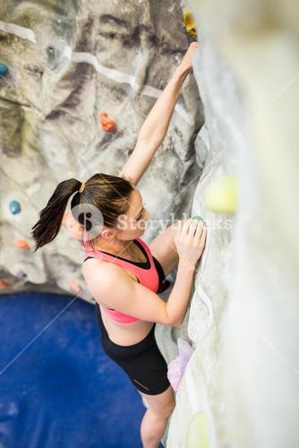 Fit woman rock climbing indoors