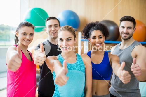 Fitness class smiling at camera in studio