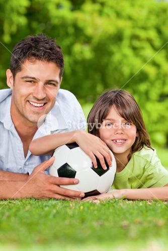 Father and his son with a soccer ball in the park