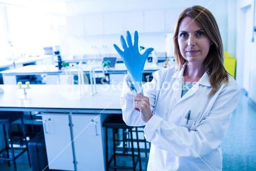 Scientist pulling on gloves in the lab