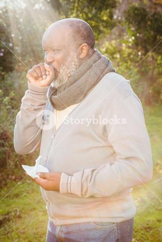 Senior man coughing with tissue