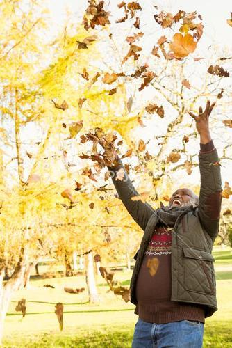 Happy old man throwing leaves around