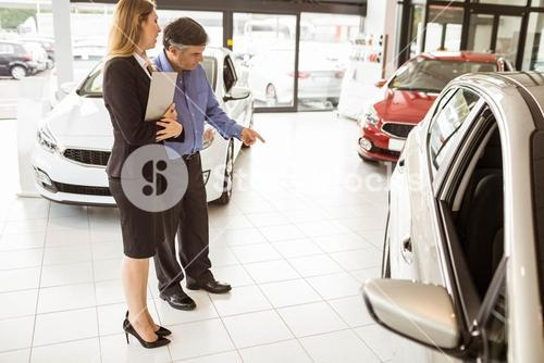A man showing a car to the saleswoman