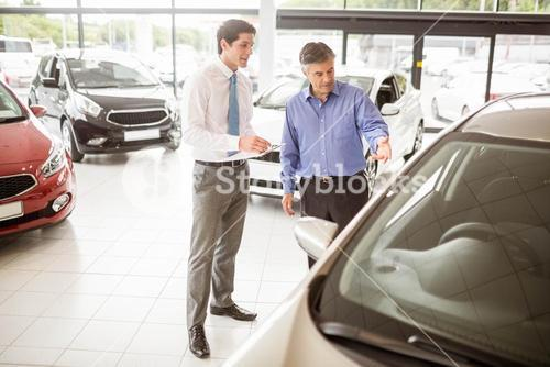 A man showing a car to the salesman