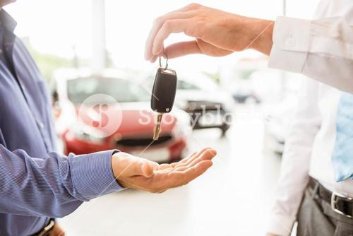 Businessman giving car key to a customer