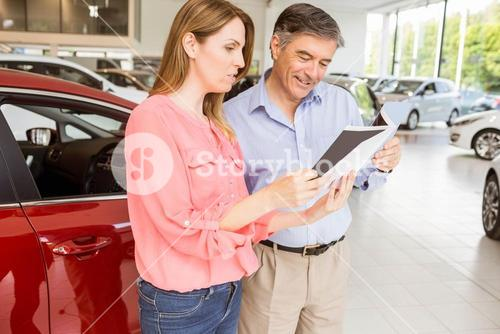 Smiling couple choosing the color of their new car