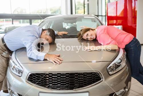 Casual smiling couple hugging their new car