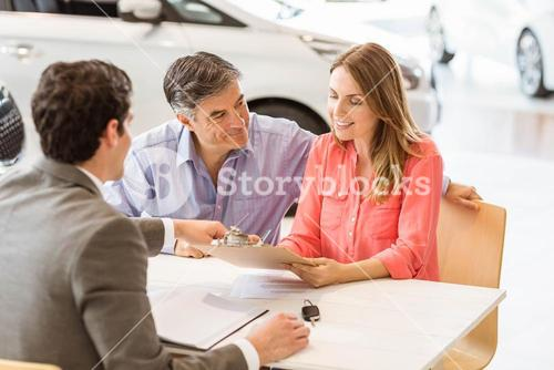 Smiling couple buying a new car