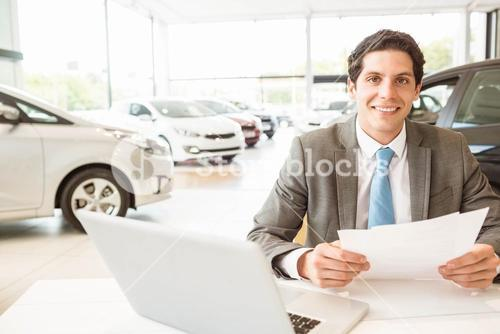 Smiling salesman reading a document