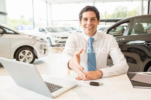 Smiling salesman ready to shake hand