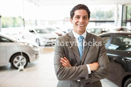Smiling salesman standing with arms crossed