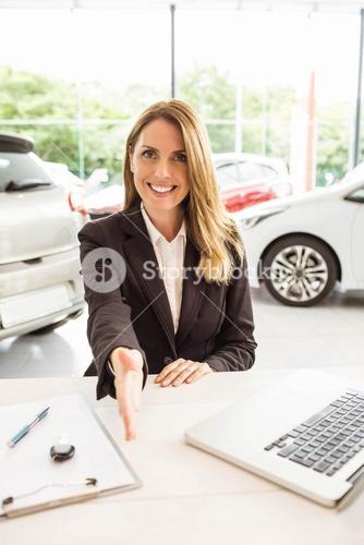 Smiling saleswoman ready to shake hand