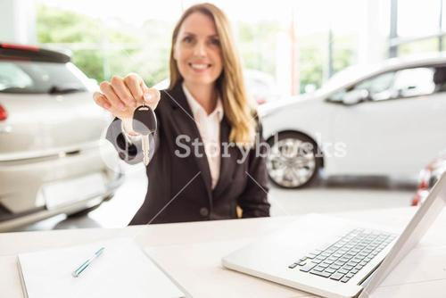 Smiling saleswoman holding car key