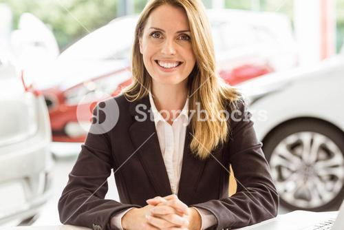 Smiling saleswoman working at her desk