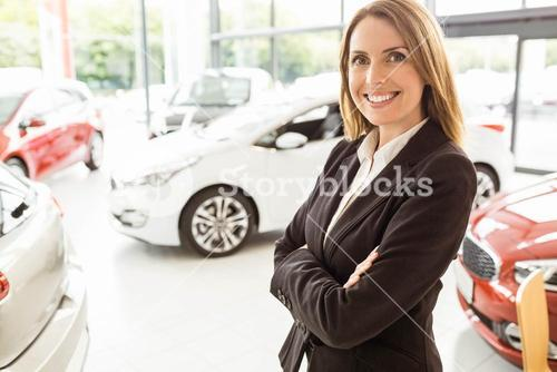 Smiling saleswoman standing with arms crossed