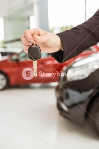 Saleswoman holding a car key