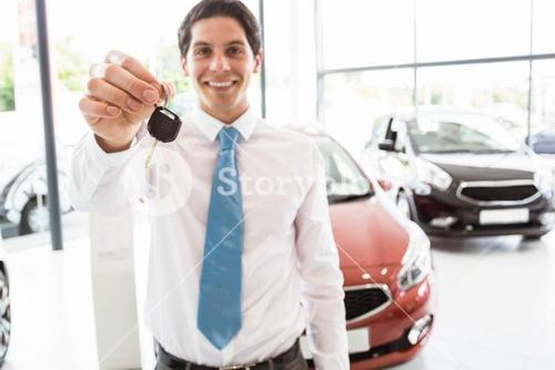 Salesman standing while offering car keys