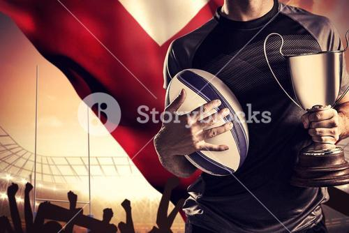 Composite image of midsection of successful rugby player holding trophy and ball