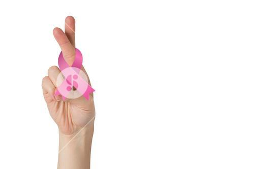 Crossed fingers with breast cancer ribbon