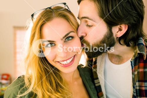 Hipster kissing his pretty colleague