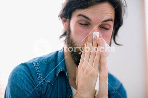 Sick man blowing his nose