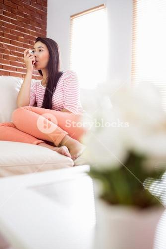 Asian woman using her inhaler on couch