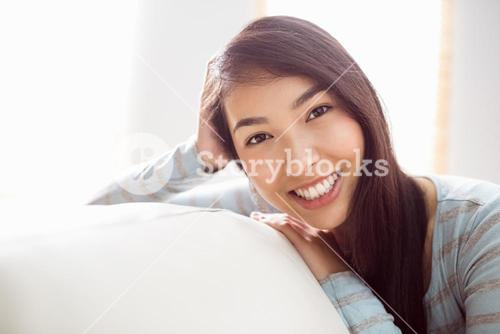 Asian woman relaxing on couch