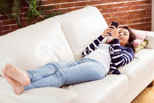 Asian woman lying on the couch using phone