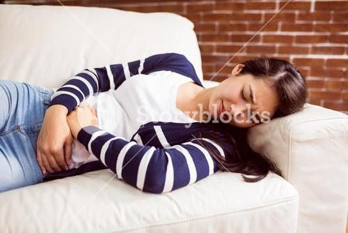 Asian woman lying on the couch with cramps
