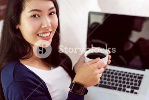 Asian woman relaxing on couch with coffee using laptop