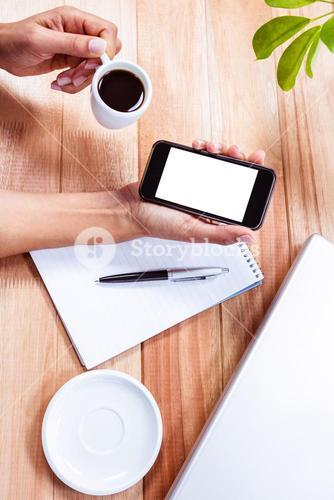 Feminine hands holding smartphone and black espresso