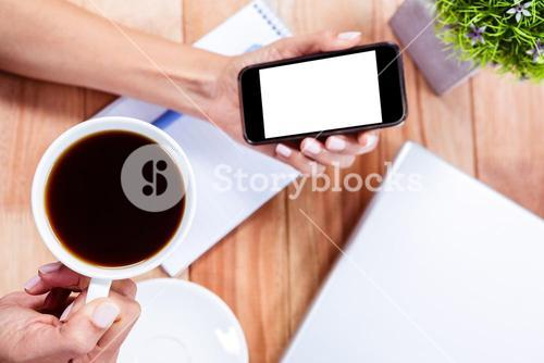 Overhead of feminine hands holding smartphone and black espresso